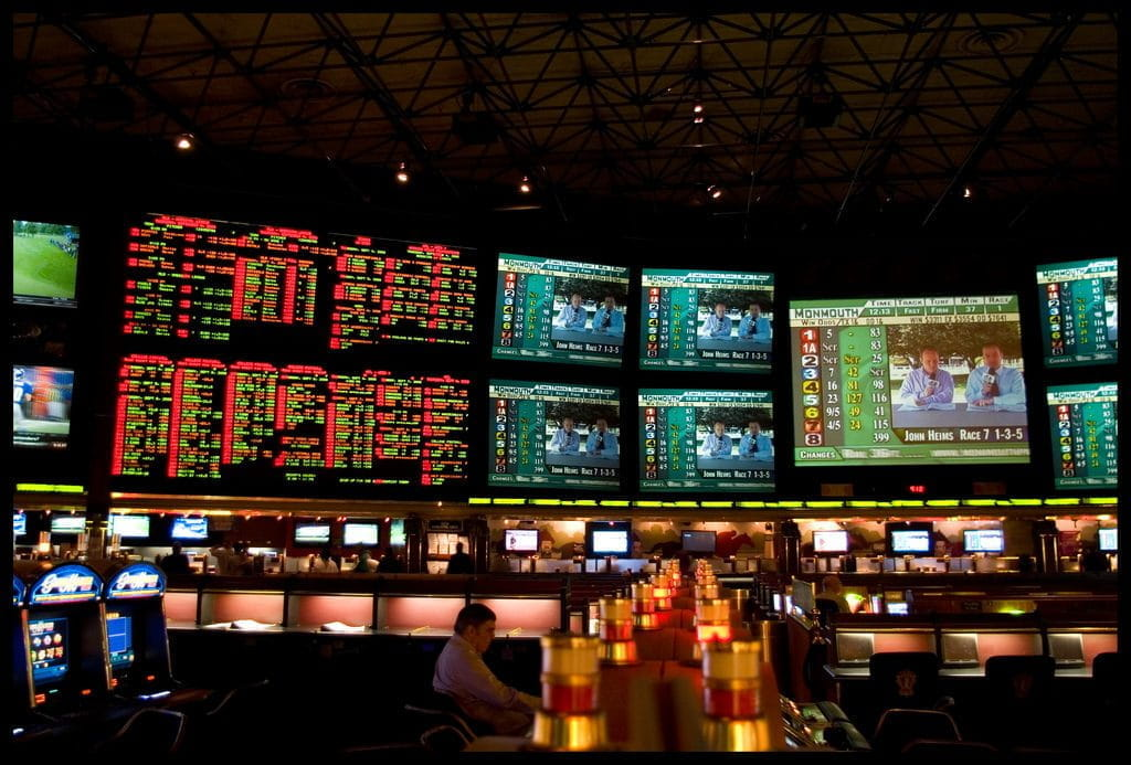 A sports betting kiosk with statistics, gameplay and odds displayed on screens.