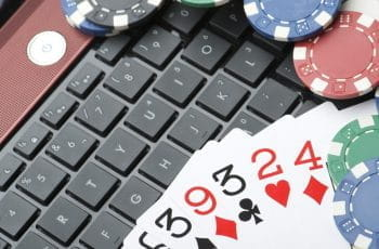 A pile of cards and poker chips stacked on a laptop's keyboard.