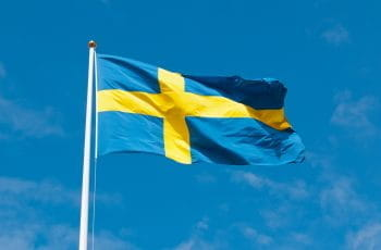 The Swedish flag flutters in the breeze against a clear blue sky..