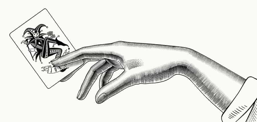 Tattoo of a hand holding a joker card.