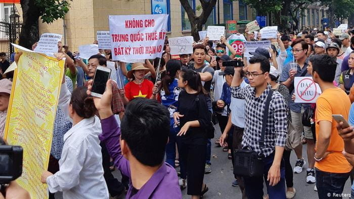Vietnamese protestors protest the new SEZ laws with picket signs.