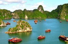 Vietnamese coastline with rocky outcrops and boats.