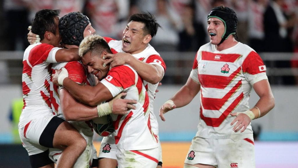 Japan's players celebrate after a try is scored by teammate.