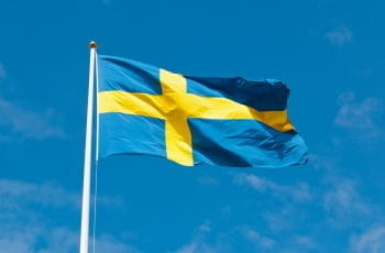 The Swedish flag on a flagpole blowing in the wind.