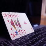 Playing cards balanced on a laptop.