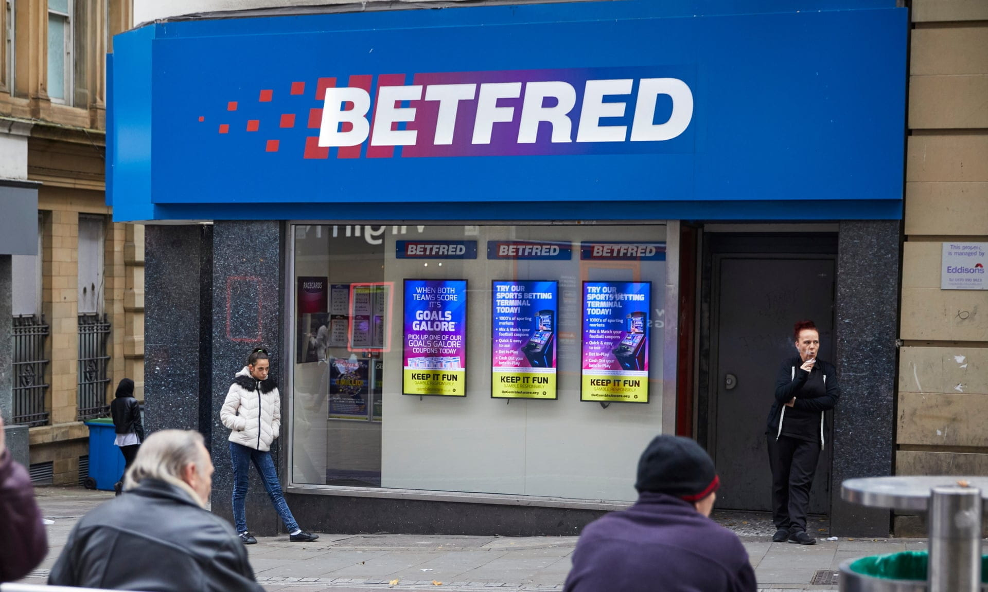 A Betfred shop on the highstreet, with members of the public walking about.