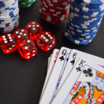 A deck of cards, stacks of poker chips and some dice on a table.
