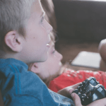 Image of two children playing together on a PlayStation.