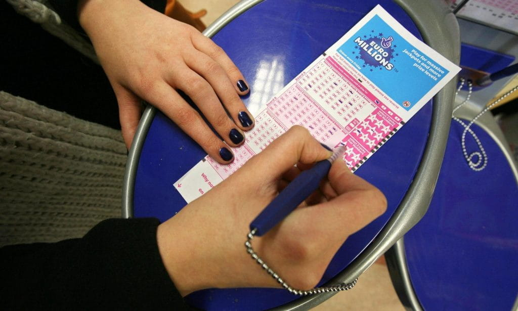 Someone filling out a EuroMillions ticket.