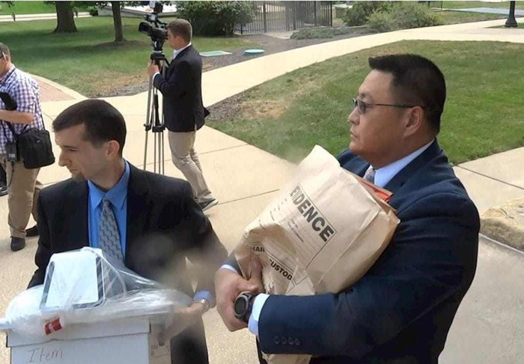 An FBI agent leaves Martin Sandoval's office with bag marked evidence.