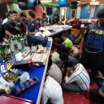 Men in police uniforms surround several tables at an illegal casino in Bangladesh, while about 10 men sit underneath the tables, their heads ducked.