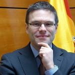 Juan Espinosa stands in an office in front of a Spanish flag.