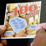 A pair of hands hold up a Lotex lottery card.