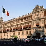 A long view of the Mexico government building, with Mexico's flag flying in front.