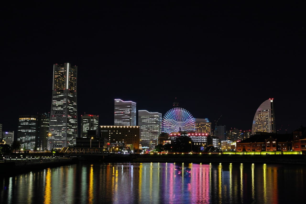 The skyline of Yokohama seen at night from the other side of the river.