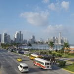 Alt Text: Panama City on a sunny day. You see a beach side street with tall skyscrapers in the background.