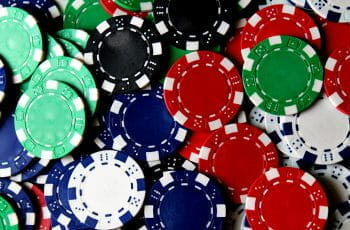 Close up of many poker chips in different colors.