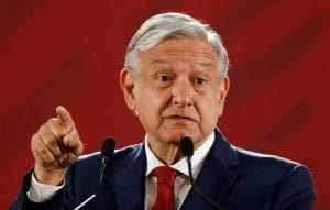 Mexico's President, Andrés Manuel López Obrador, speaks in front of a red curtain.