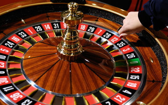 A hand dips onto a spinning. roulette wheel.