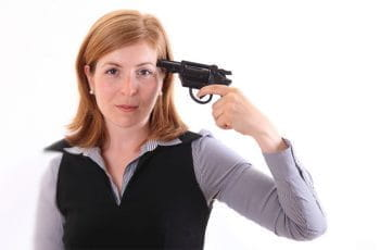 A woman holding a gun to her head.