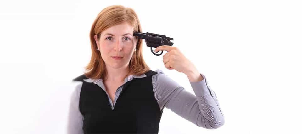 A woman holding a gun to her head.