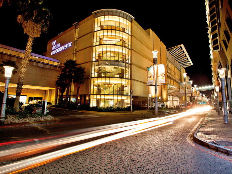 The Sandton Convention Centre seen from the street at twilight.