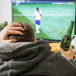 A man clutches his head and a beer bottle while watching a football match on TV.