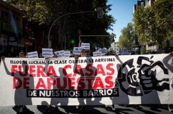 Protestors in Spain hold up a big white banner and signs to demonstrate against the gaming industry.