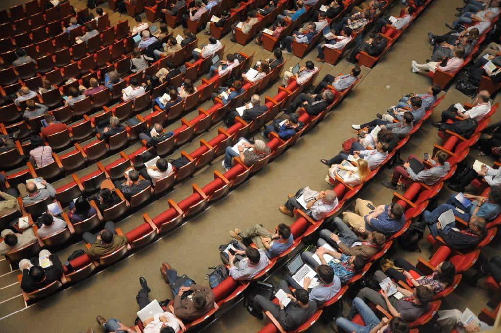 A birds-eye view of people sitting in theater seats.