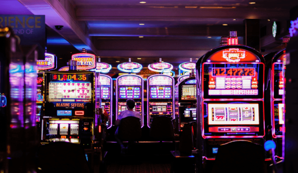 Bright and colorful slot machines light up casino floor.