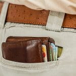 A stuffed wallet with credit cards in a pair of khaki pants.