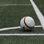 A soccer ball (football) sits positioned in the corner of a grassy field.