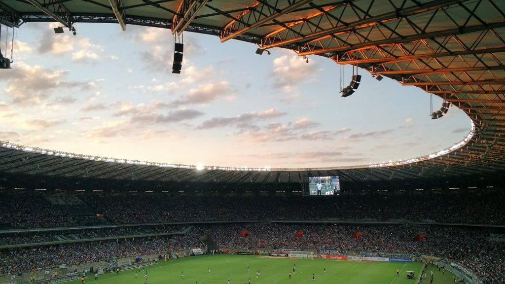 A sweeping shot of inside a football (soccer) stadium as game play continues.