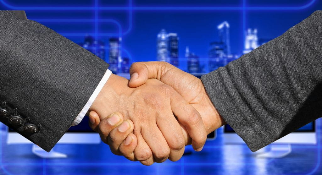Two hands of businessmen meet in the middle to shake hands.