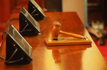 A judge's gavel rests on a judge's stand.