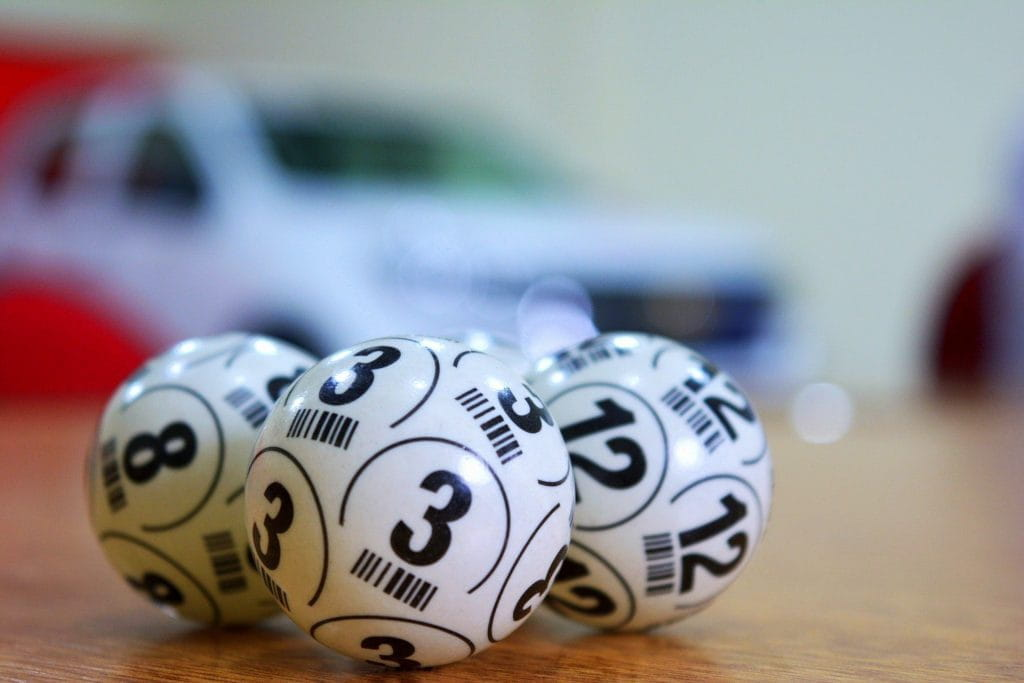 Black and white numbered lottery balls against a blurred background.