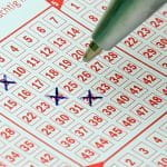 A pen crosses off numbers on a lottery ticket.