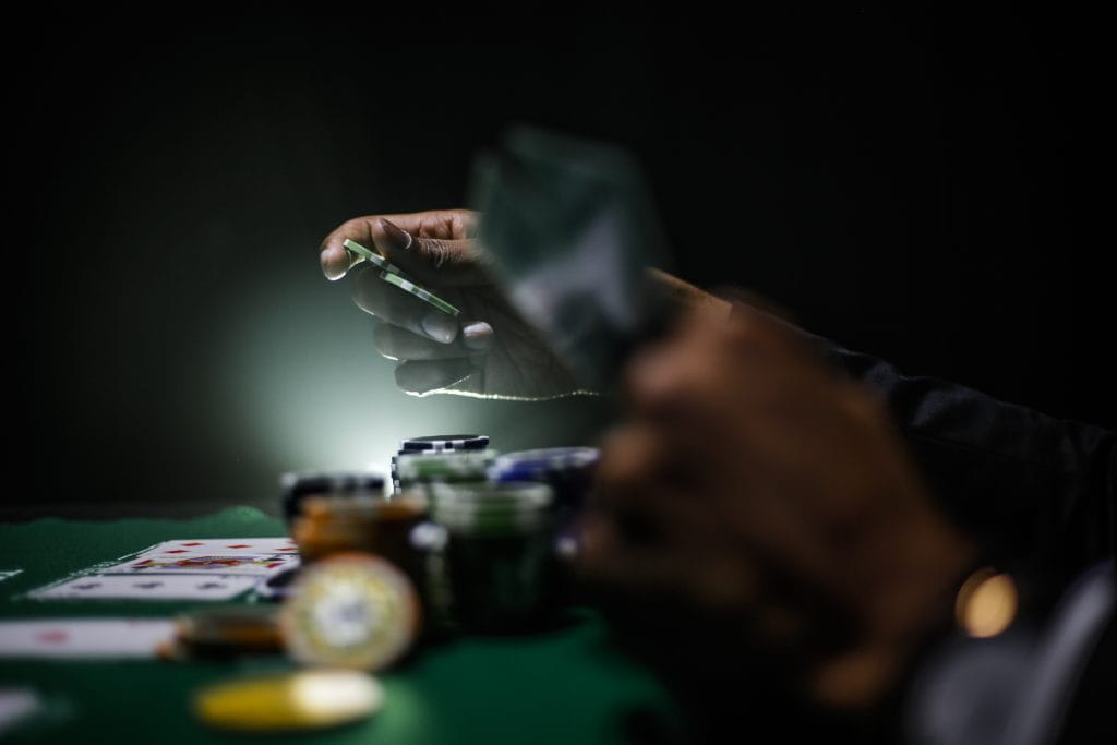A player lays down cards at a poker table beside stacks of chips.