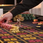 A casino dealer places chips on the table.