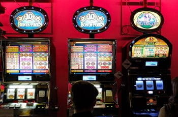 Three slot machines against a red wall in a casino.