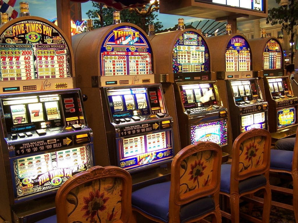 A row of slot machines in a brightly lit casino.