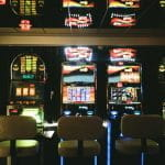 Three colorful slot machines in a dimly lit casino.