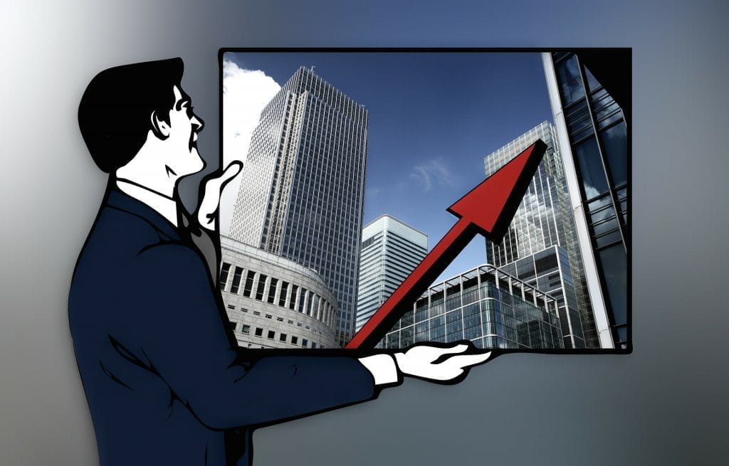 A graphic of a man in a suit holding a large photograph of skyscrapers. Superimposed over the skyscrapers is a large red arrow pointing up.