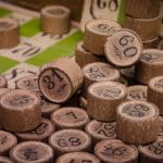 A pile of wooden cylinders with numbers on them, as if from a bingo game.