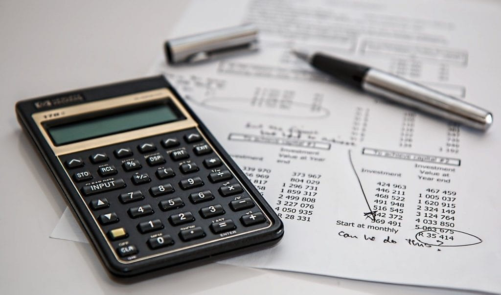 A calculator and a pen on a sheet of paper with account information.
