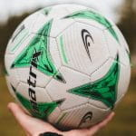 A green and white football held up in a person's hand.