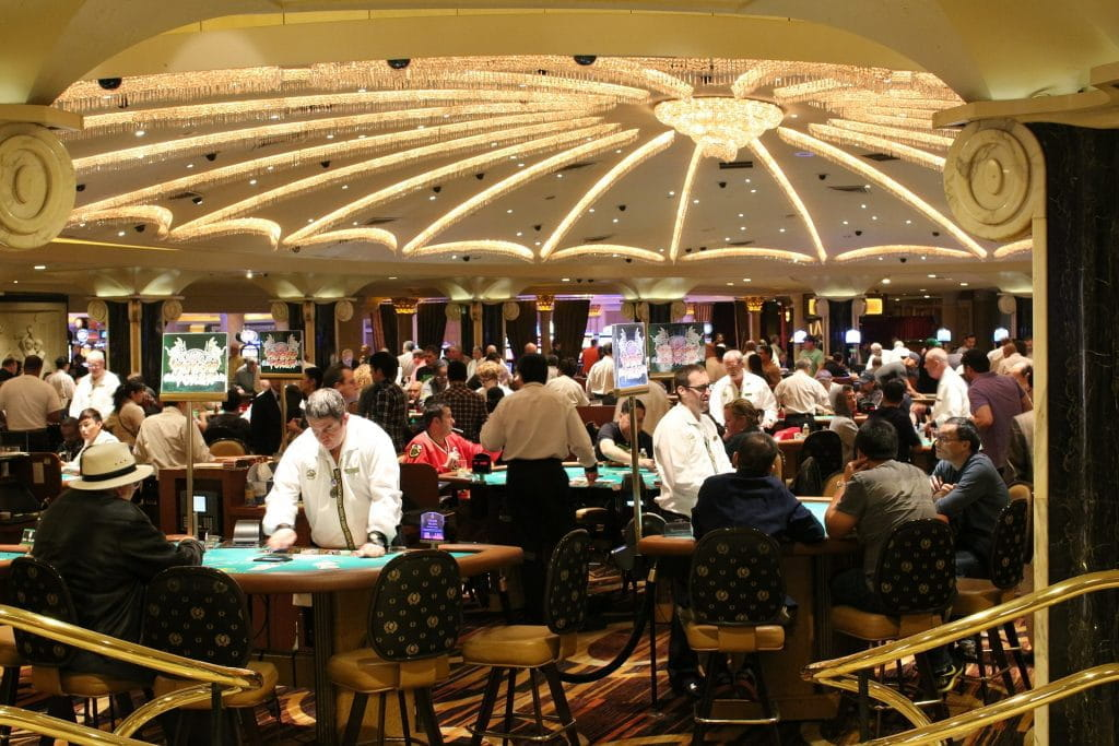 A gaming hall with people playing table games like poker and blackjack.