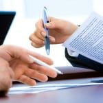 Two white hands holding pens and paper poise to sign an agreement.