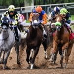 Horses racing on a dirt track.