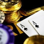 Poker chips and gold coins next to two Ace playing cards.